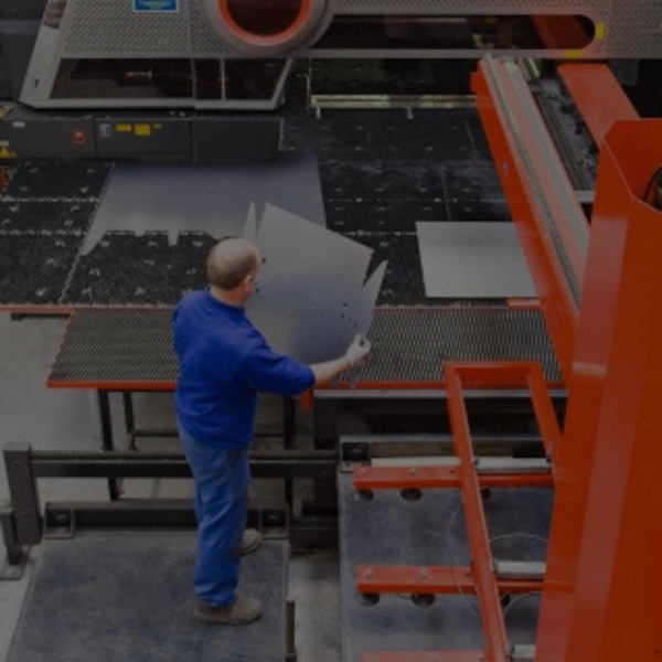 Man standing by sheet metal press in factory